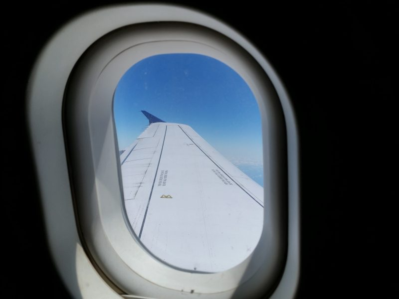 Looking out an airplane window at the wing with a blue sky beyond.