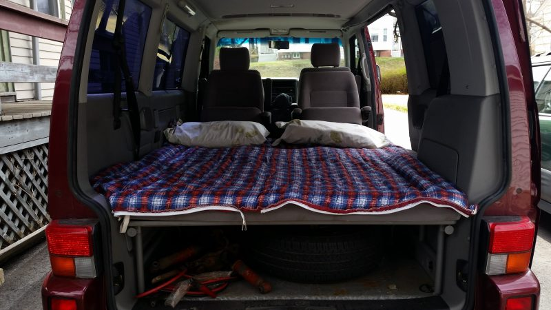 A grey interior of a burgundy Volkswagen Eurovan with a sleeping bag spread out.