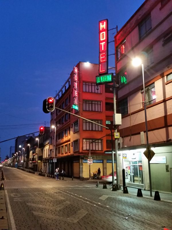 Two backpacker hotels in Mexico on the corner of the street in the evening with glowing neon signs.