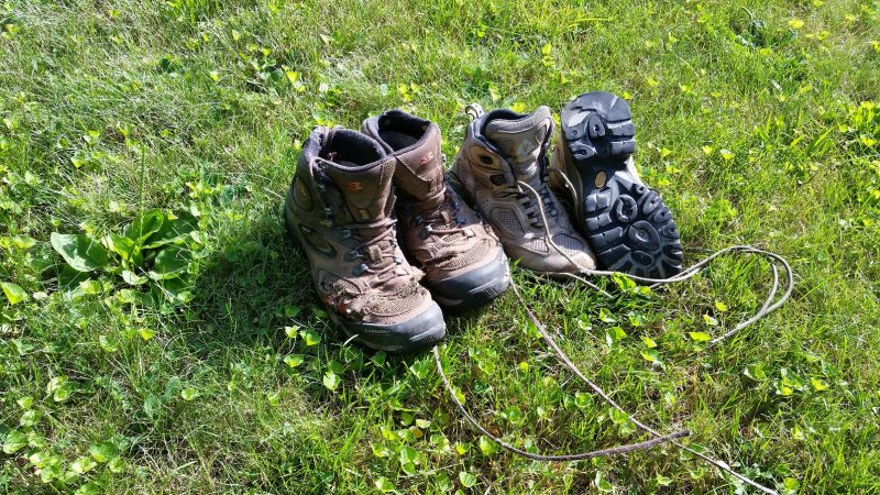 Two very worn pairs of hiking boots on a patch of green grass.