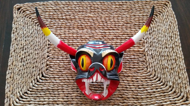 A brightly colored wood mask of a bat's face with horns from Tocuaro, Mexico on a woven mat.