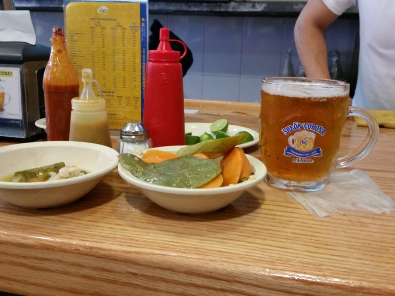 A bowl of pickled vegetables and a glass mug of beer sitting on a wooden counter with some condiment bottles in the background.