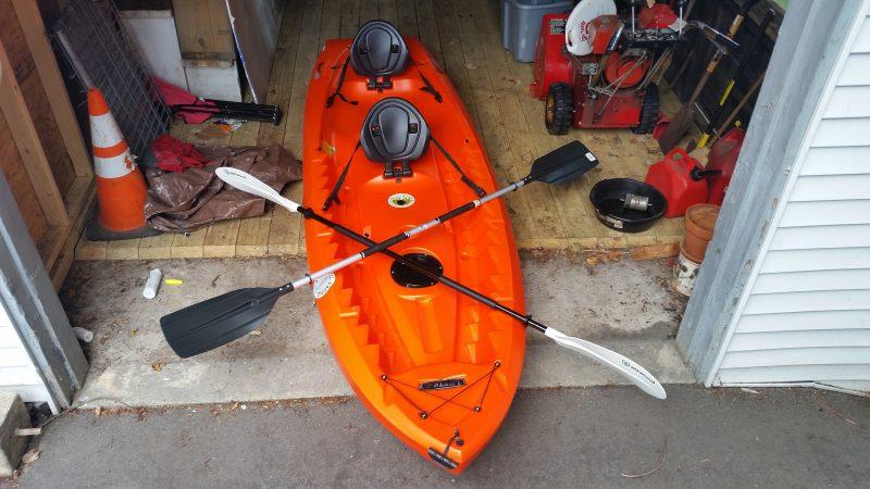 Orange kayak in a garage.