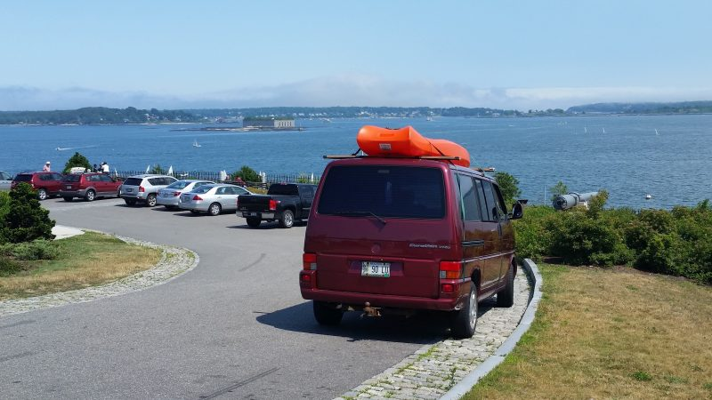 Burgundy Volkswagen van with an orange kayak on top of it and a bay in the background.