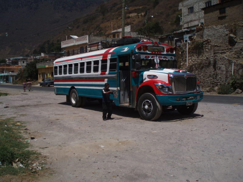 Man holding a rag standing next to a brightly-colored chicken bus in Zunil, Guatemala.