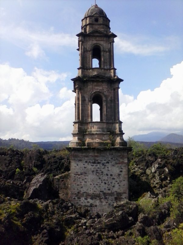 A church tower buried partially buried by Volcan Paracutin poking out of the ground in the state of Michoacan, mexico.,
