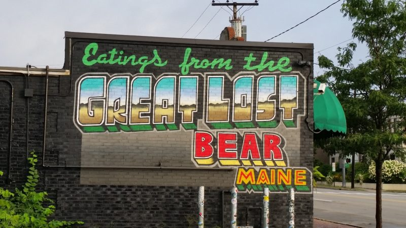 A colorful mural for The Great Lost Bear on the side of a brick building.