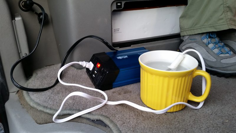 Yellow coffee mug with a heating element plugged into a power inverter.