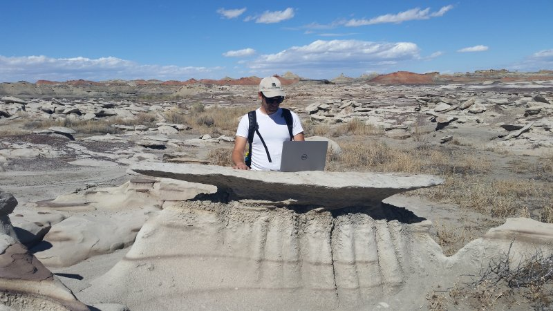 Man on rock formation using a laptop computer.