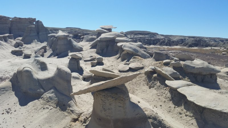 Several mushroom-shaped rock formations against a blue sky at Bisti/De-Na-Zin Badlands in New Mexico.