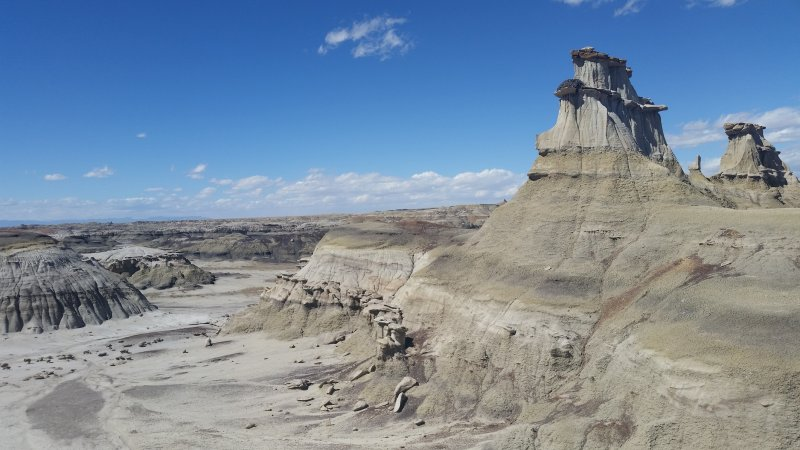 Many differently shaped rock formations against a blue sky at Bisti Badlands.