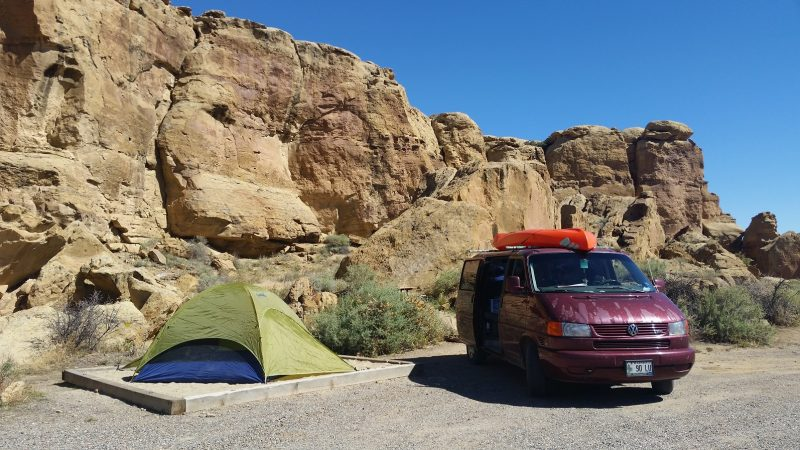 A burgundy Volkswagen van and a green and blue tent at a Chaco Canyon camping site.