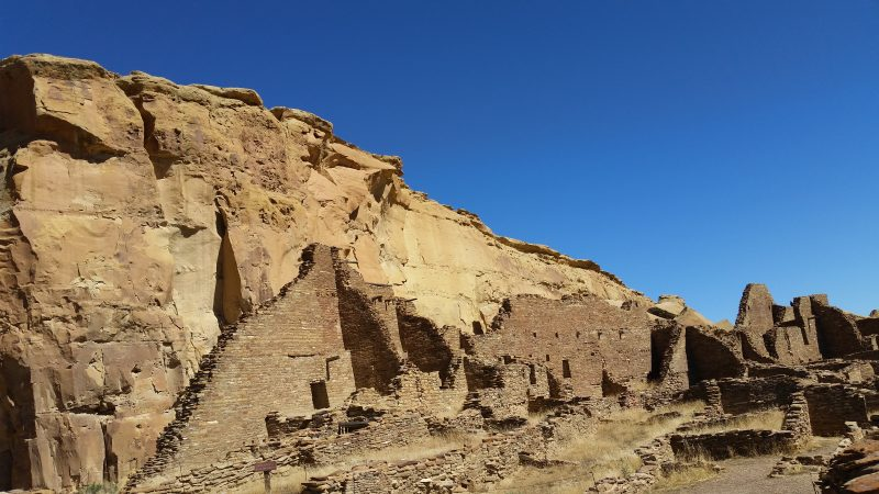 pueblo ruins against a sheer red cliff and blue sky.