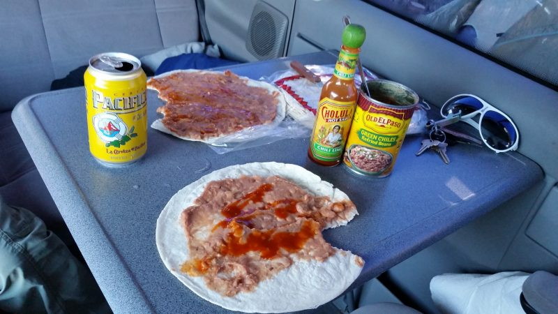 Beans, tortillas, Cholula sauce and Pacifico beer on a grey table.