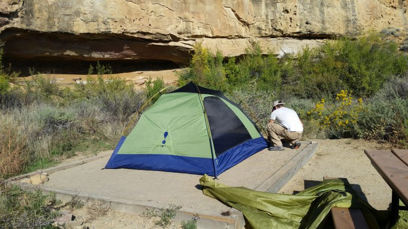 man setting up a green tent next to rock wall