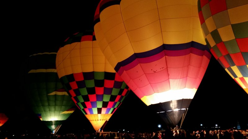 Tethered hot air balloons with their burners glowing in the dark at the Albuquerque International Balloon Fiesta.