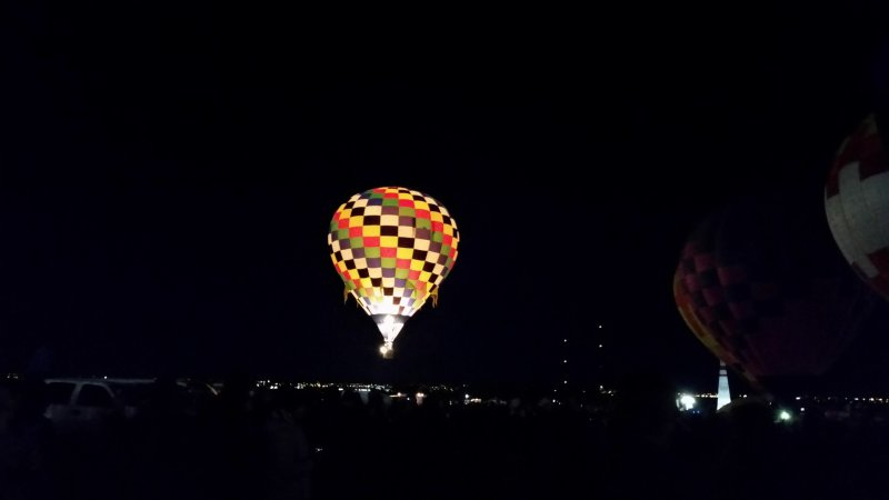 a hot air balloon glowing against a dark sky.