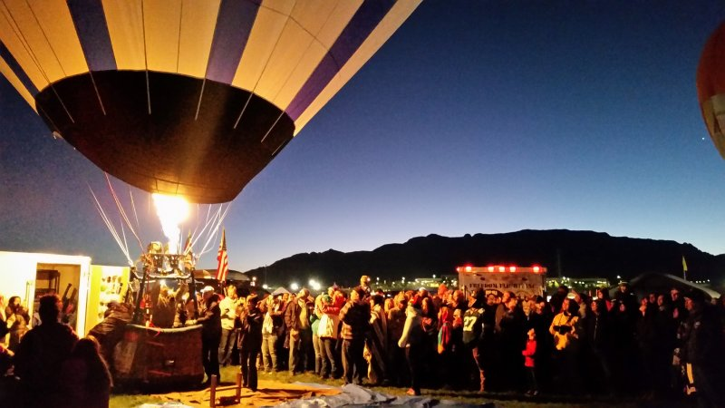 Many people gathered around a glowing hot air balloon in the early morning light.