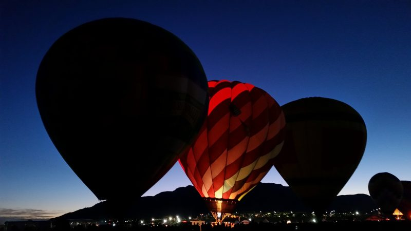 Hot air balloons in silhouette but with one glowing at the break of dawn at the Albuquerque International Balloon Fiesta with Sandia Mountains in background.