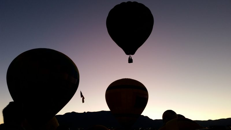 Hot air balloons taking off into the early morning sky with the Sandia Mountains beyond
