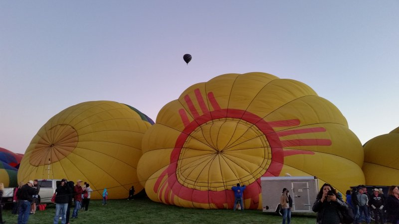 A hot air balloon being inflated featuring the zia symbol of New Mexico at the Albuquerque International Balloon Fiesta.
