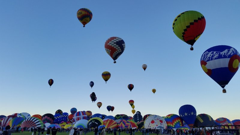 Hundreds of hot air balloons on the ground in varying stages of inflation at the Albuquerque International Balloon Fiesta.