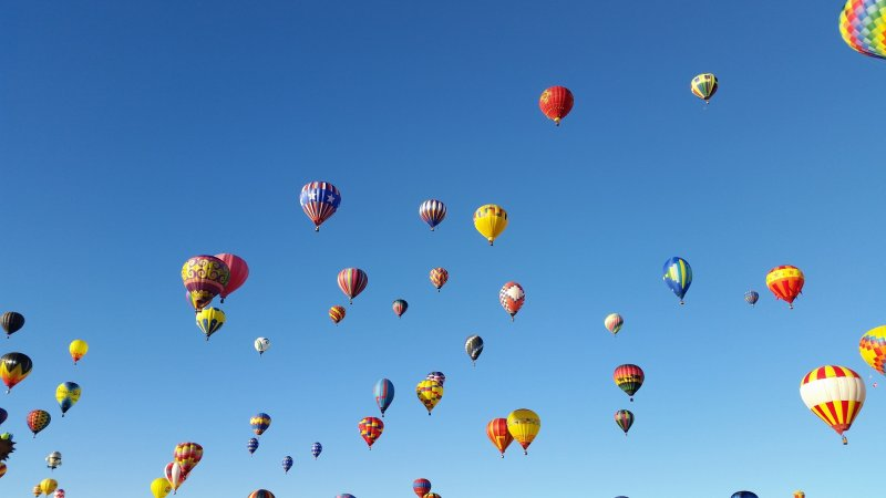An all blue sky with about 30 hot air balloons floating.