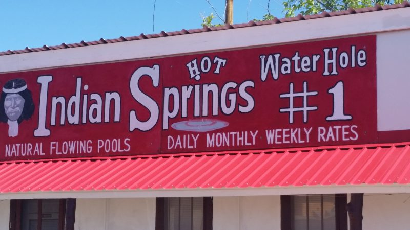 A red sign advertising Indian Springs Baths in Truth or Consequences, New Mexico.