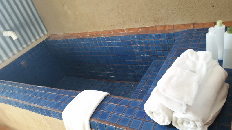 A blue tiled bathtub with a white towel on the edge of it.