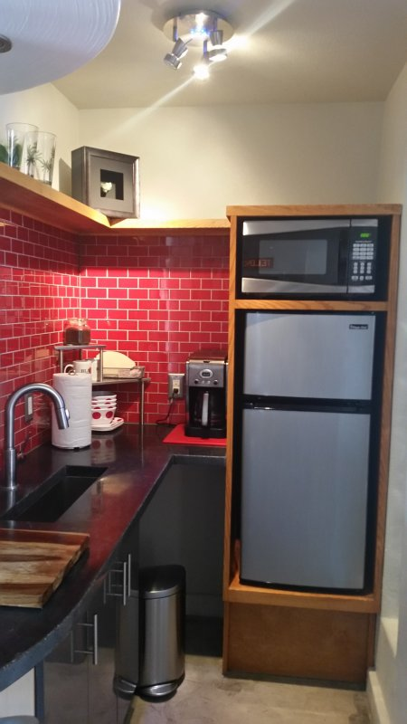 Kitchen with red tiles and a stailess steel fridge.