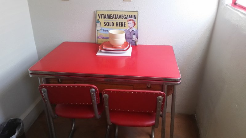 A red table with two red chairs and several saucers on top.