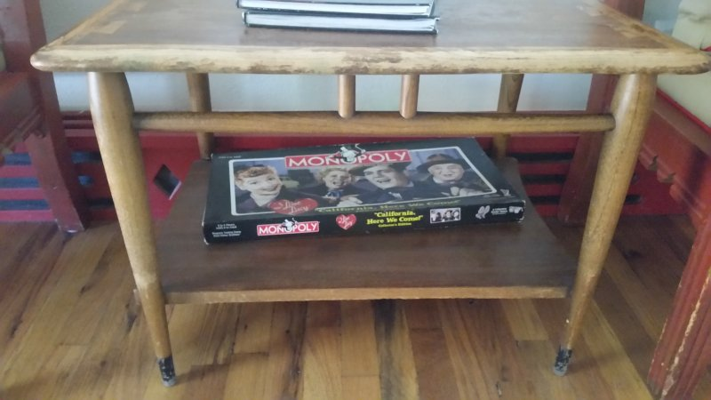 An I love Lucy version of a Monopoly game sitting on the lower shelf of a table.