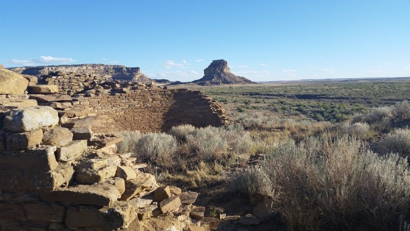 Several ruins among desert scrub with a mesa or butte in the background at Chaco Canyon National Historic Park.
