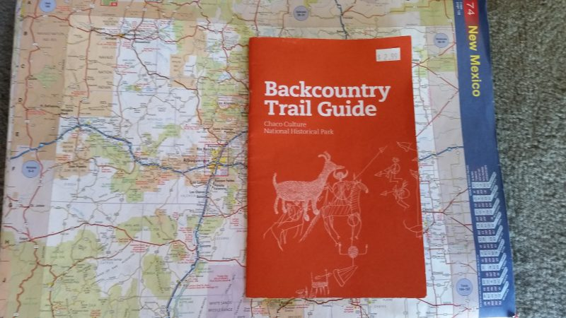 A Chaco Canyon Backcountry Trail Guide sitting on top of a road atlas.
