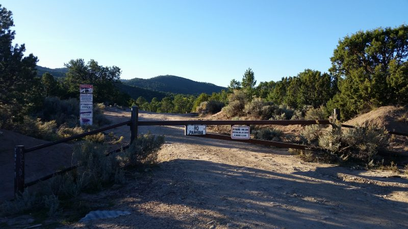 A closed gate with several signs on it going across the old road to Ponce de Leon hot springs near Taos, New Mexico.