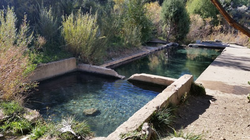 Two old concrete pools filled with clear hot spring water.