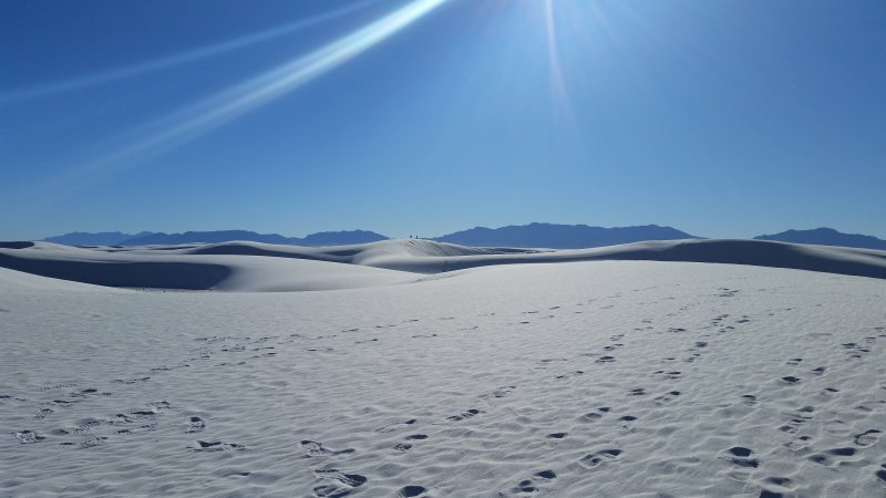 Several sand dunes against a blue sky at White Sands National Monument, one of the most popular places to go in New Mexico.