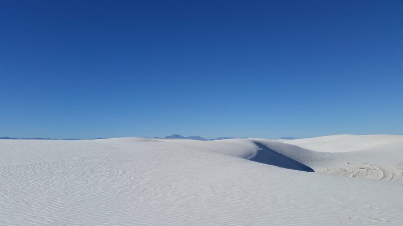 A white sand dune against a clear blue sky.