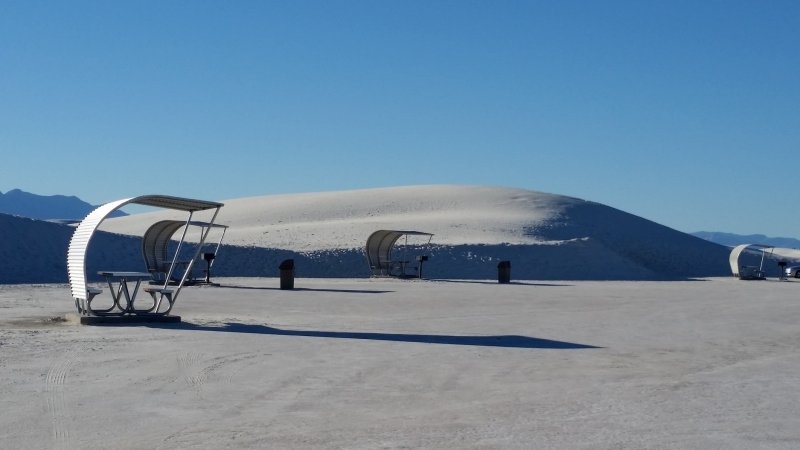 Four picnic shelters surrounded by white sand dunes resembling snow near Alamogordo.