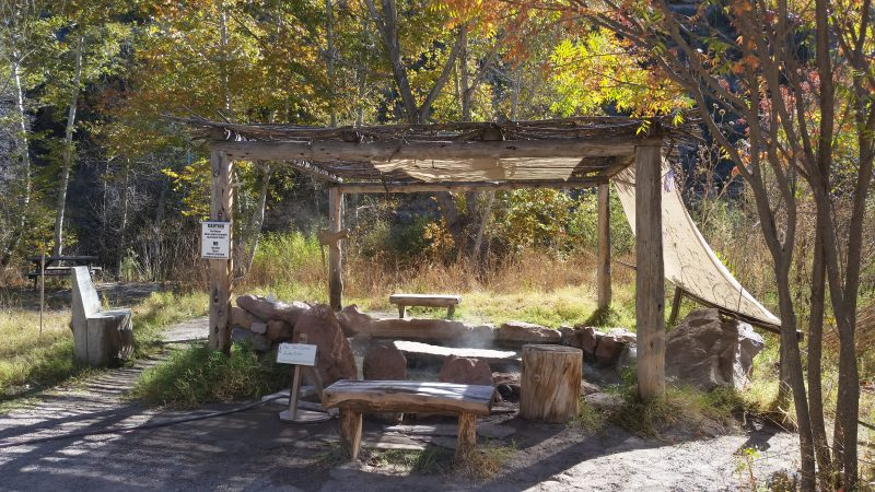 Hot springs with wooden benches and overhead canvas canopy.
