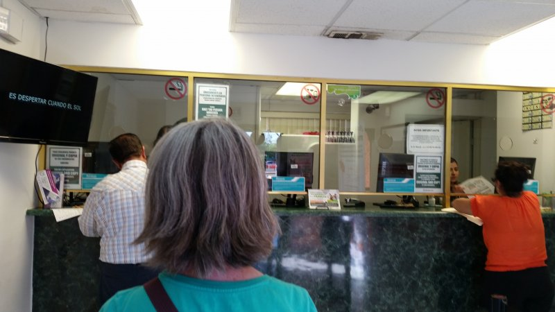A woman standing in line while others pay for a car permit before driving in Mexico at a Banjercito office located in Mexicali.