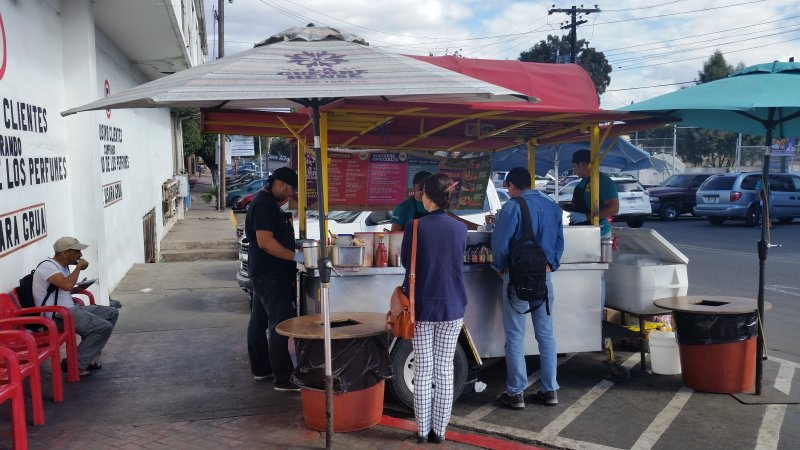 A food cart with customers ordering and eating seafood in Ensenada, Mexico.