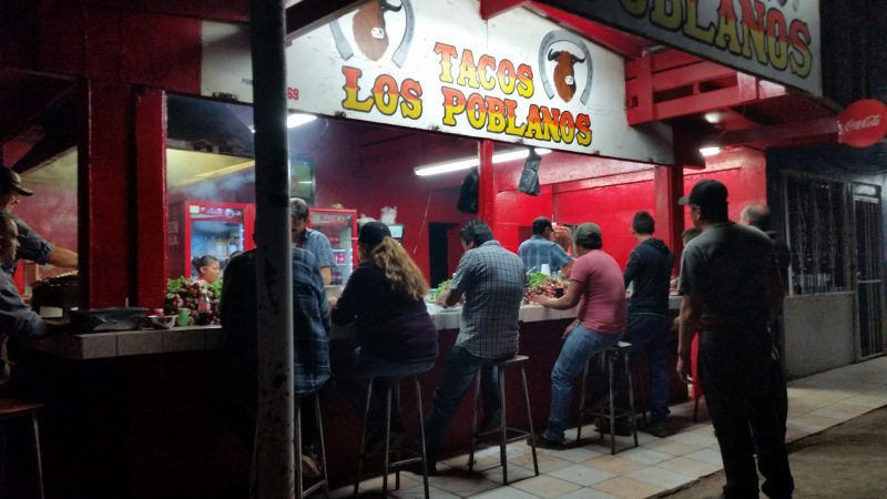 Customers sitting at an outdoor taco stand in San Quintin, Mexico.