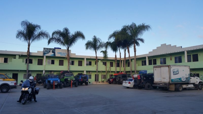 A parking lot of a green-painted hotel with palm trees and vehicles in San Quintin, Baja California.