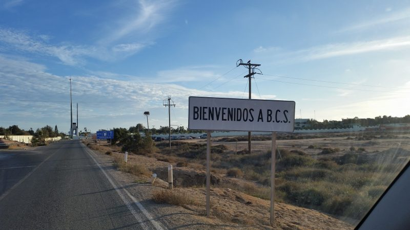 A white welcome sign with black lettering seen during a state border crossing on a Baja Mexico road trip.