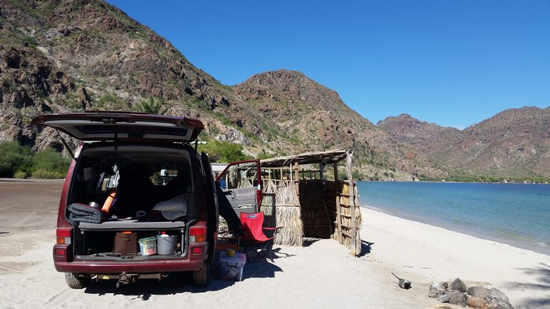 A Volkswagen van Baja California camping on a white sand beach with mountains in the background.