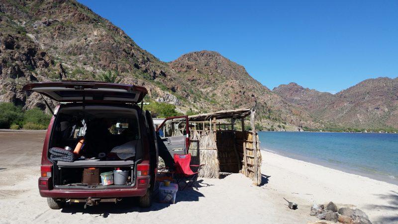 Volkswagen van baja camping on a white sand beach