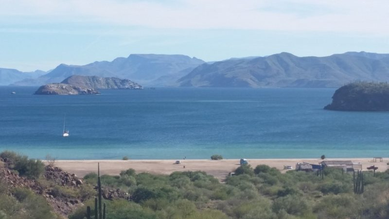 View of beach with vehicles baja camping on the sand