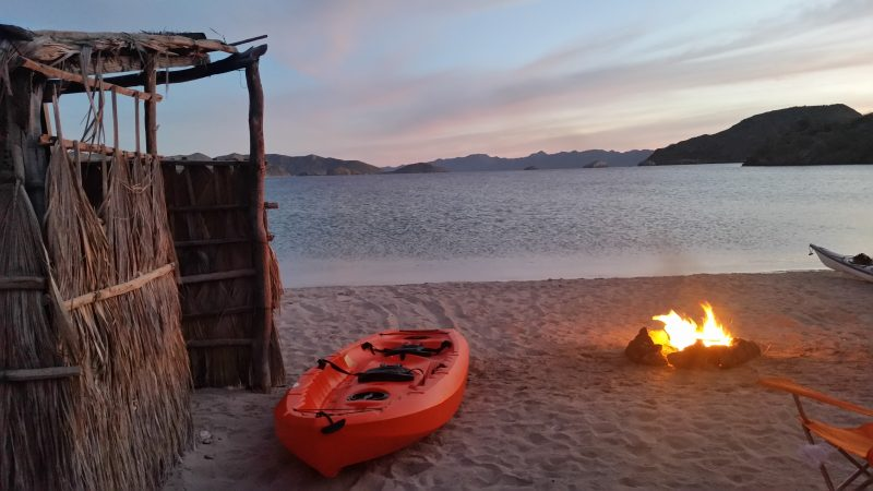 An orange kayak on the beach by a campfire with purple sunset in the background.