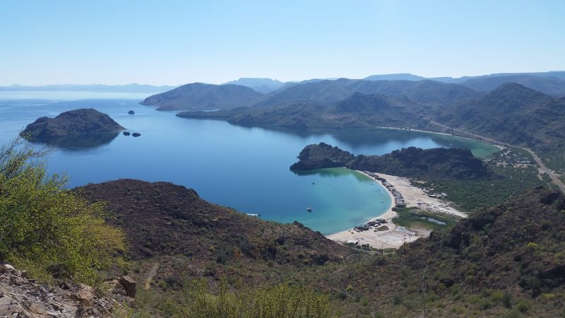 A view of two beaches with white sand and blue water full of people camping in Baja California.